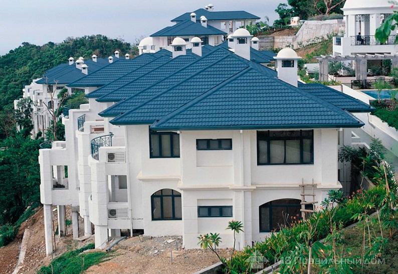Синяя крыша из композитной черепицы на доме с белым фасадом